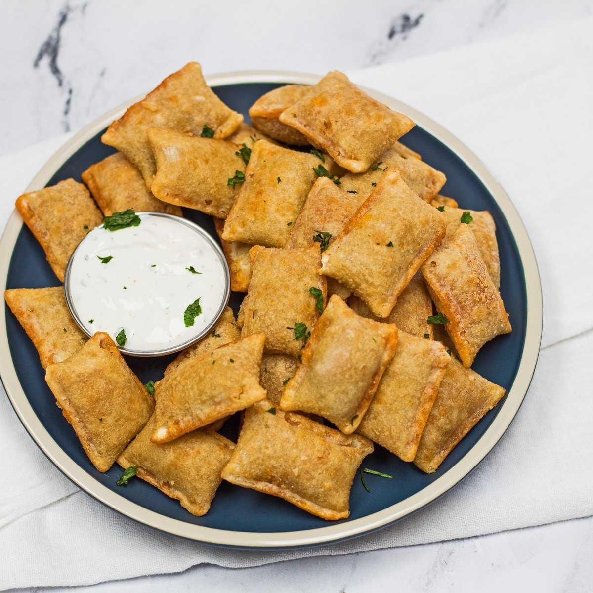 Frozen pizza rolls cooked in the air fryer and served with dipping sauce.