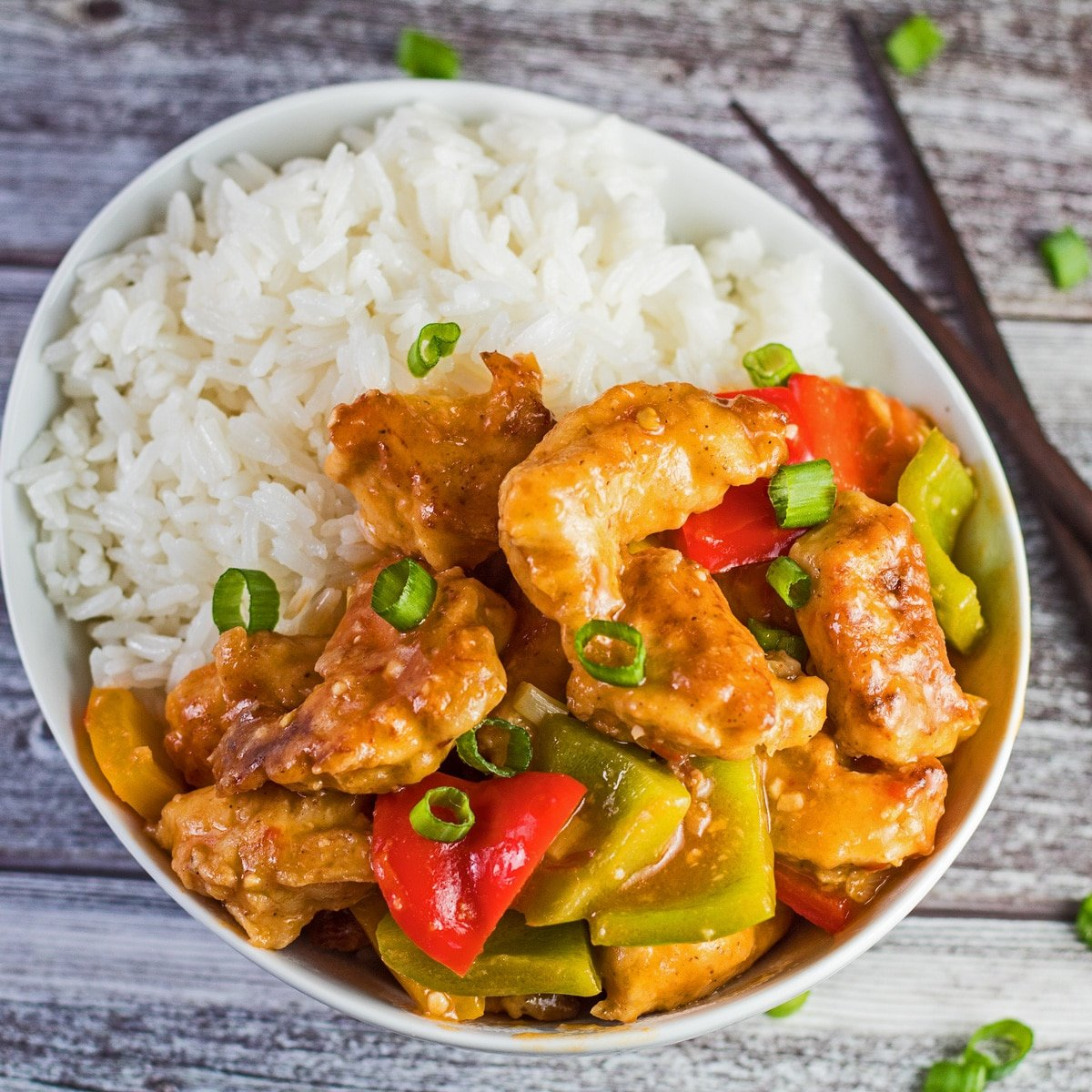 Chicken manchurian served on rice in a white bowl.