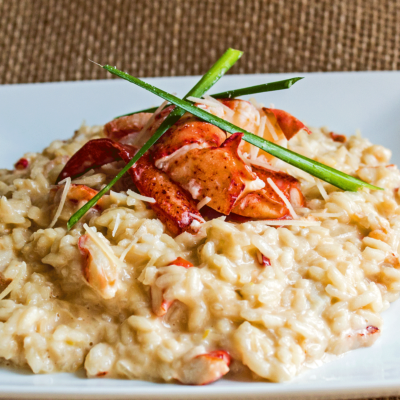 Creamy lobster risotto garnished with lobster claw and chives.