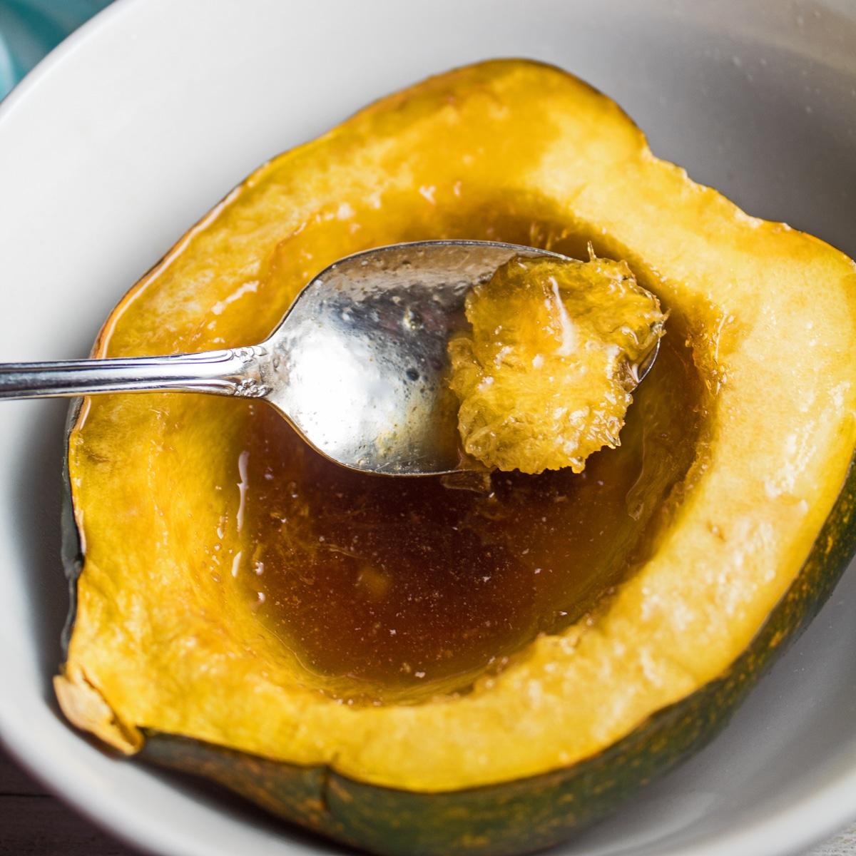 Mjuk mikrovågs ekollon squash serveras i vit skål.