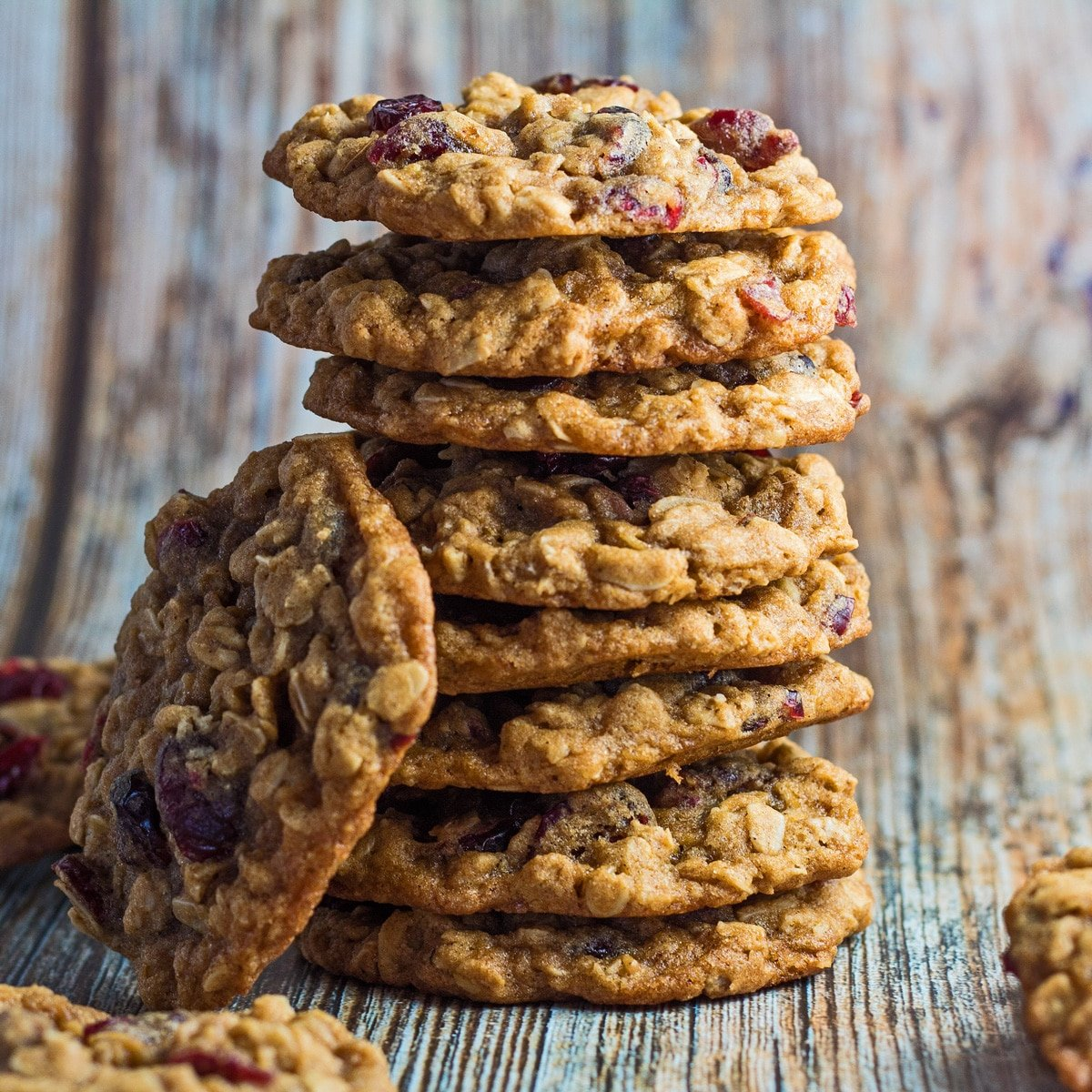 Oatmeal craisin cookies stacked with wooden grain background.