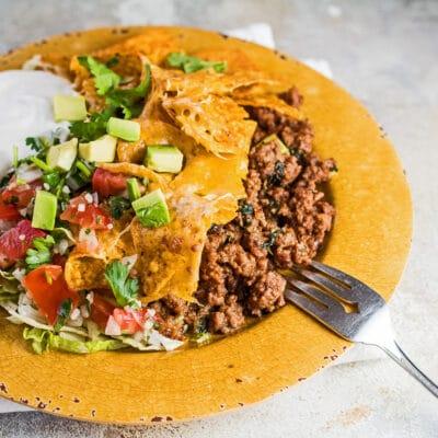 Promenad taco gryta serverad med sallad, gräddfil, pico de gallo och avokado.