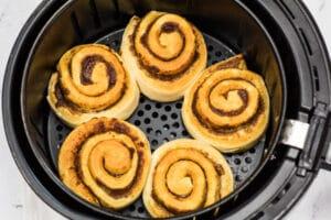 Vérification des brioches à la cannelle après 8 minutes dans la friteuse à air.