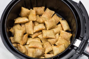 Flip or toss air fried pizza rolls at halfway point in cooking before finishing.