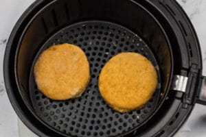Frozen chicken patties placed into air fryer basket.