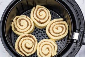 Rouleaux de cannelle crus placés dans le panier de la friteuse à air.