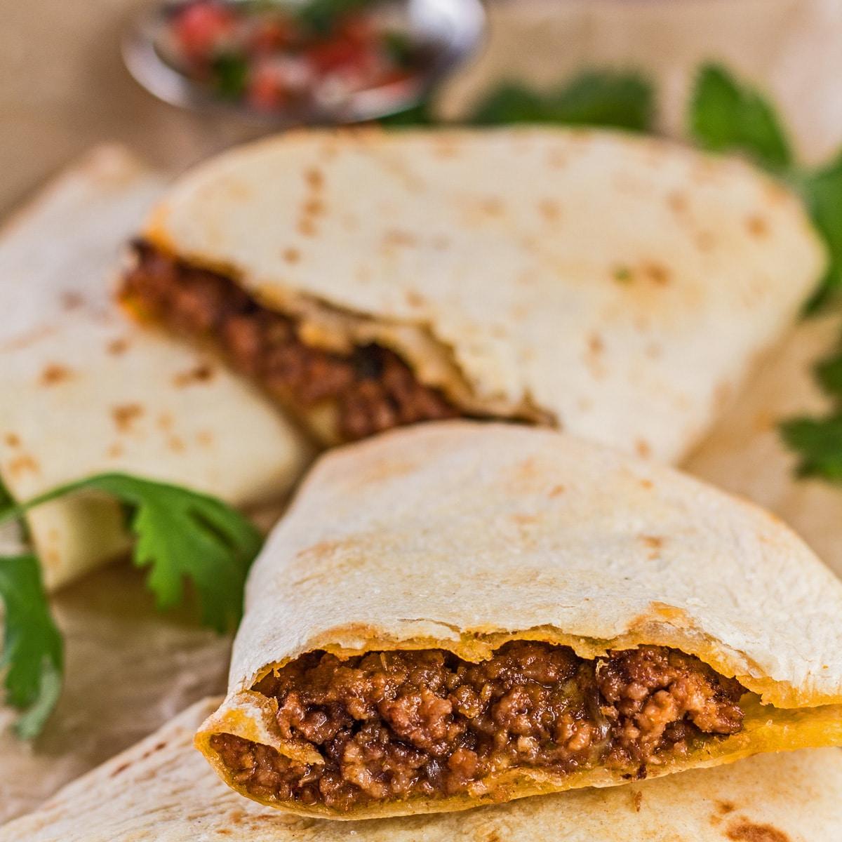 Quesadillas friteuse à air sur planche à découper avec pico de gallo en arrière-plan.