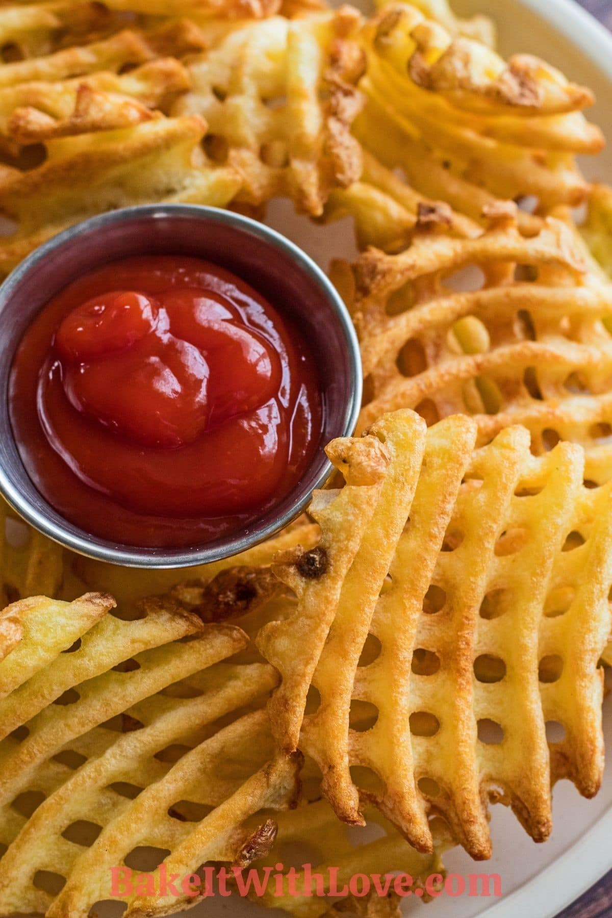 Waffle Fries cooked in an air fryer and served on plate with ketchup.