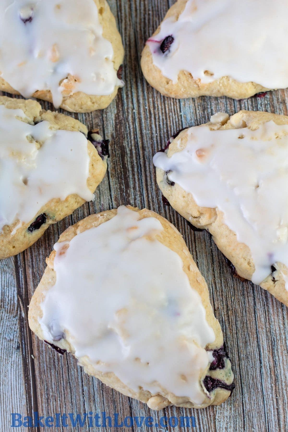 木製の背景にレモンのアイシングと5つのブルーベリーホワイトチョコレートスコーン。