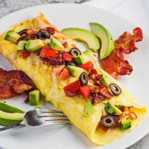 Beyaz tabakta pastırma ve avokado ile California omleti.