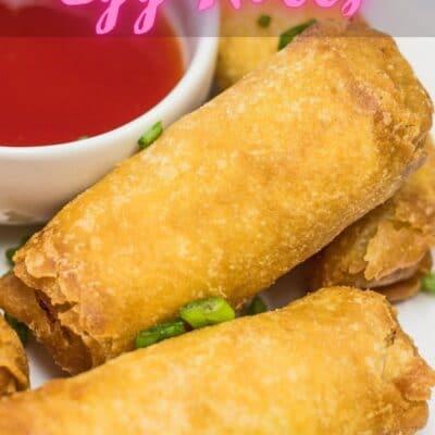 مقلاة هوائية لفائف البيض المجمدة مطبوخة على طبق أبيض مع تراكب نص.
