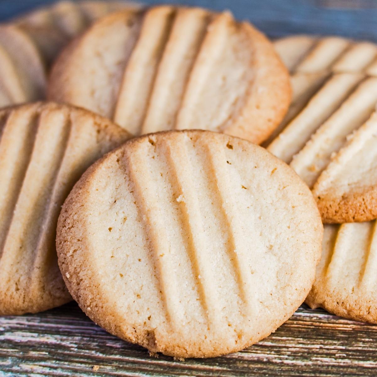 Fork biscuits baked until golden and randomly piled onto wooden grain background.