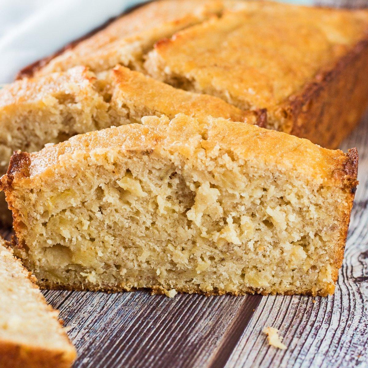 Sliced pineapple banana bread on wooden grain background.