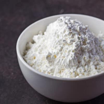 Potato starch shown in white bowl on dark background.