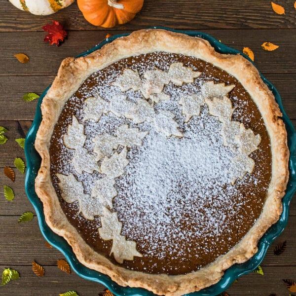 Pumpkin Pie in green pie plate on wooden background.