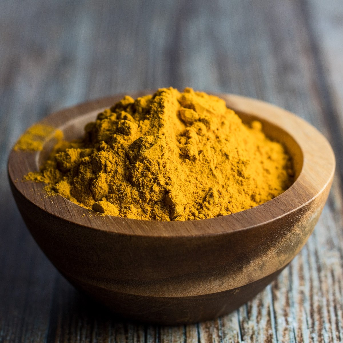Loose ground turmeric in wooden bowl on wooden grain background.
