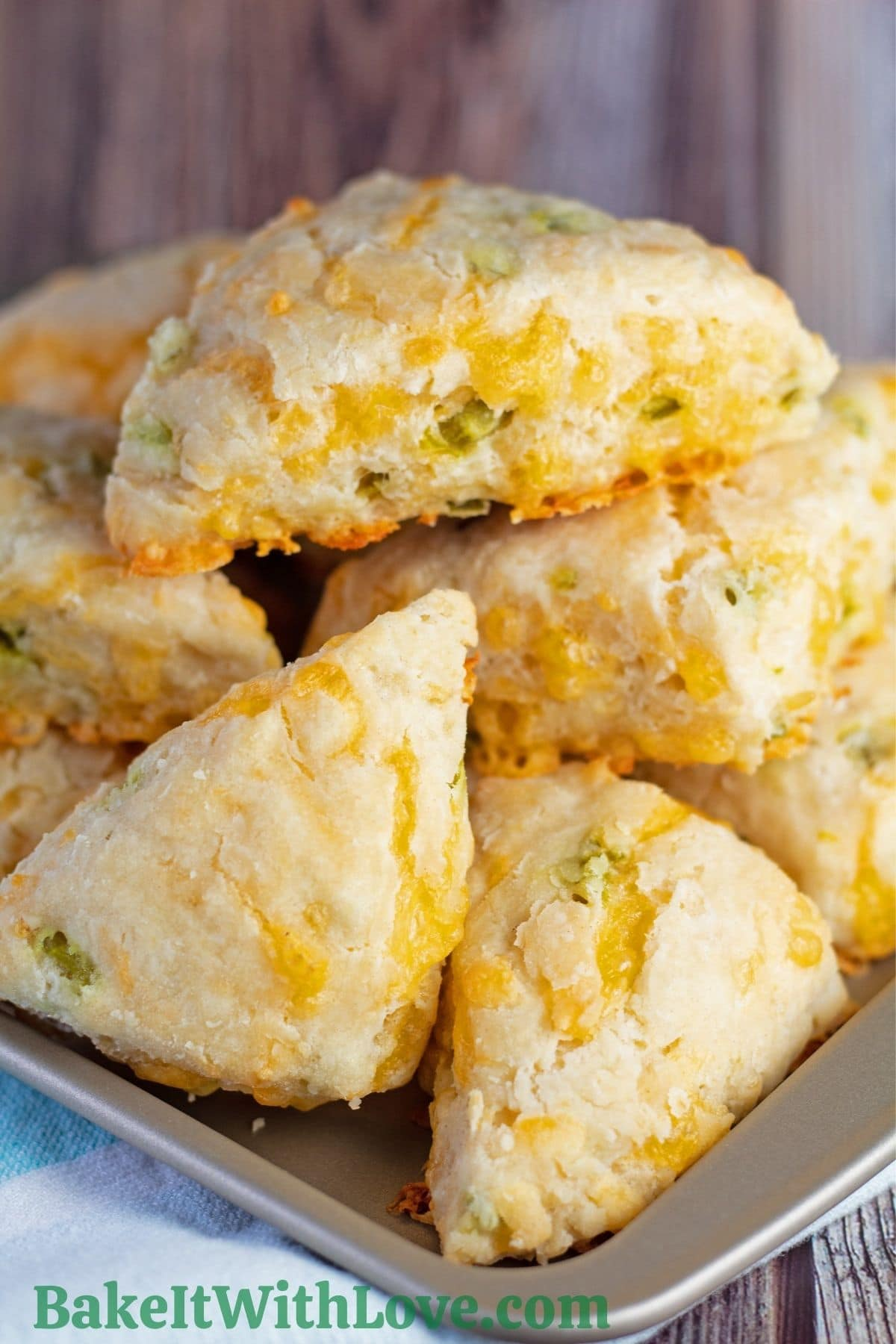 Jalapeno Cheddar Scones piled up on a baking tray with a blue and white background.