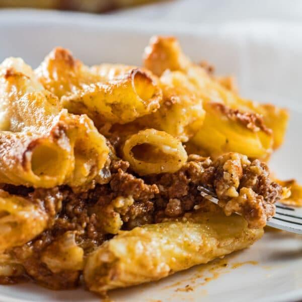 Layered bechamel pasta bake or macarona bechamel served on white dish.