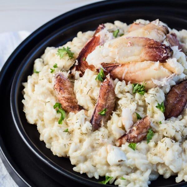 Krabberisotto serveret på sort tallerken med krabbekød og persillegarnering.