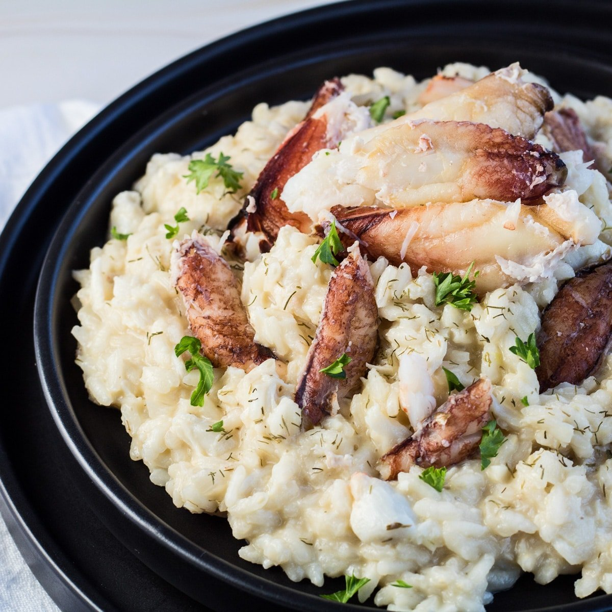 Crab risotto served on blackplate with crab meat and parsley garnish.