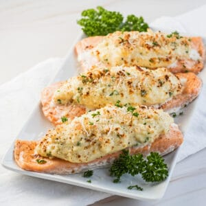Crab stuffed salmon served on white plate garnished with fresh parsley.