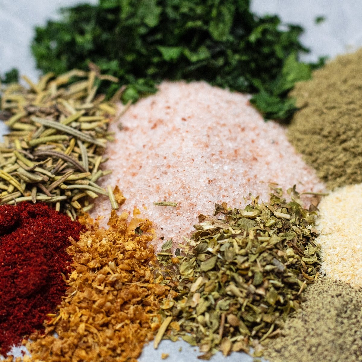 Lamb rub spices in small piles on a white background.