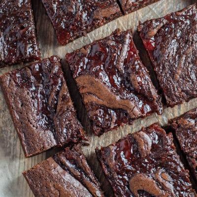 Strawberry swirl brownies dipotong dan diletakkan di atas kertas perkamen.