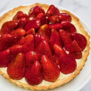 Tarte aux白いケーキスタンドに表示される、クラシックなフレンチストロベリータルトをフレイズします。