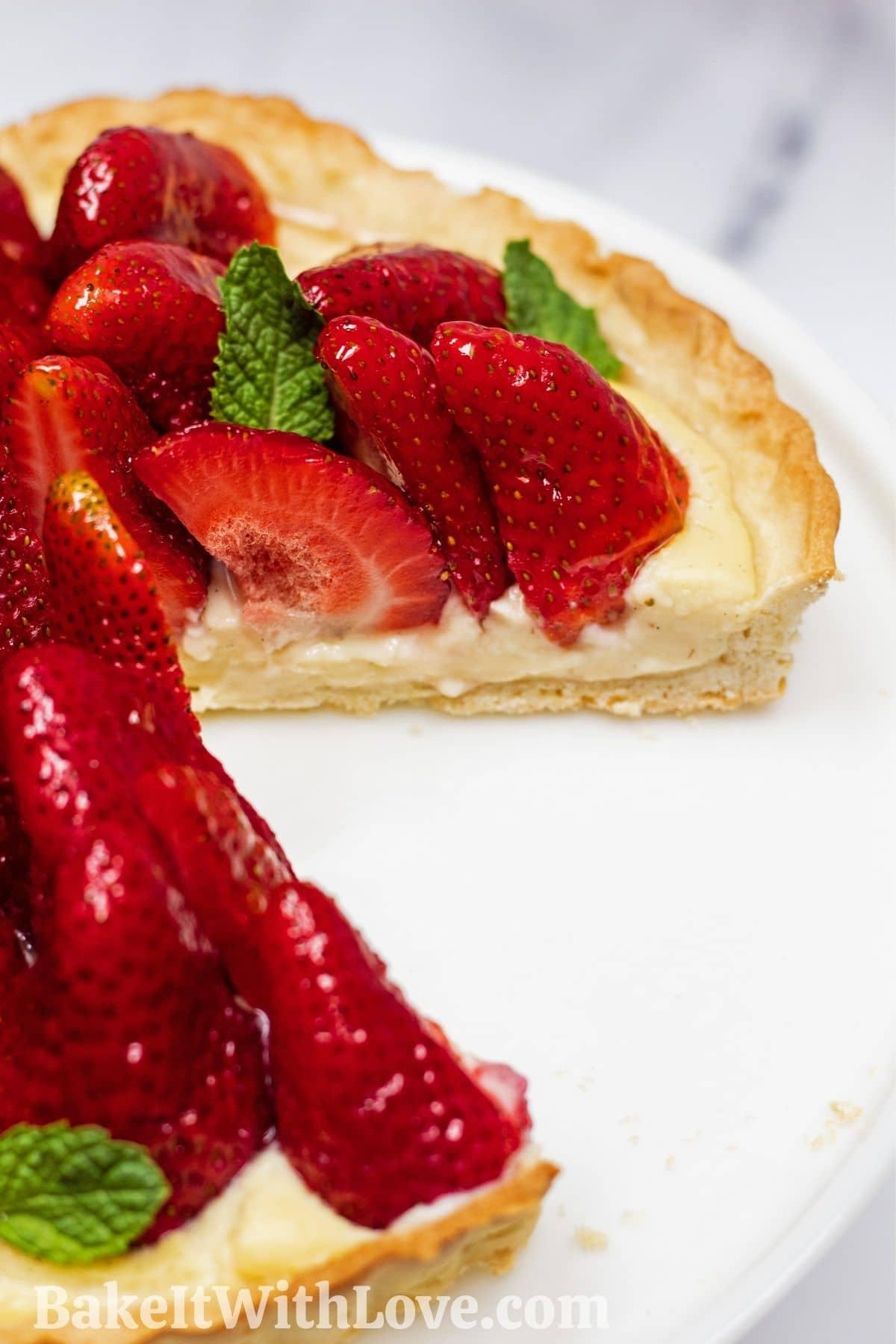 Tarte aux Fraisesは、スライスを切り取った白いケーキスタンドに表示されるクラシックなフレンチストロベリータルトです。