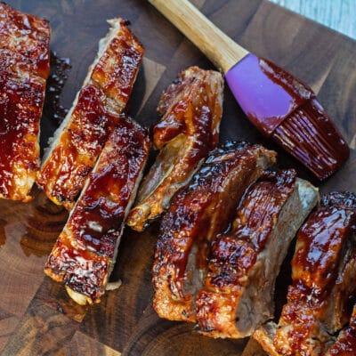 Sliced air fryer pork ribs on dark wooden cutting board.