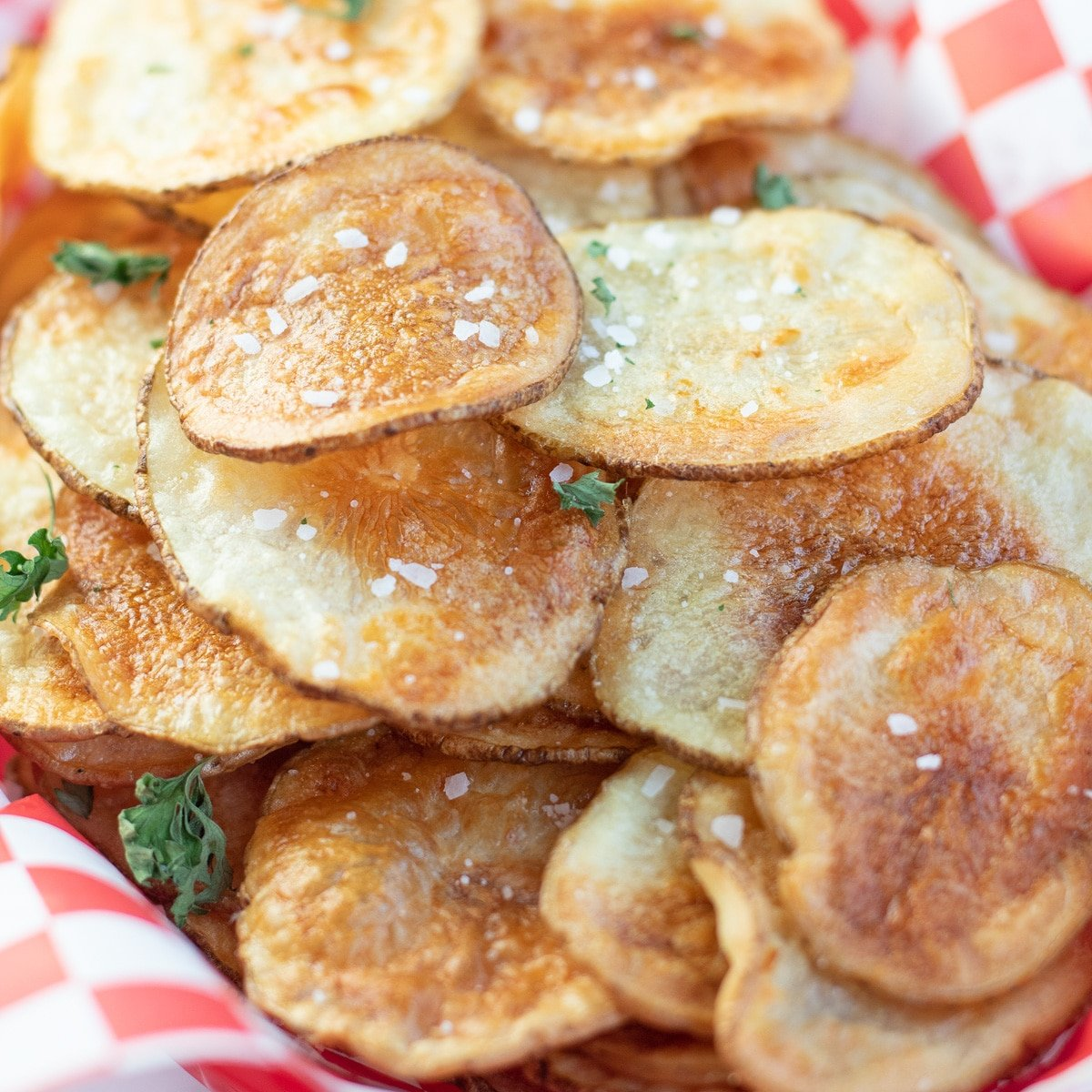 Piled air fryer potato chips in a picnic basket.