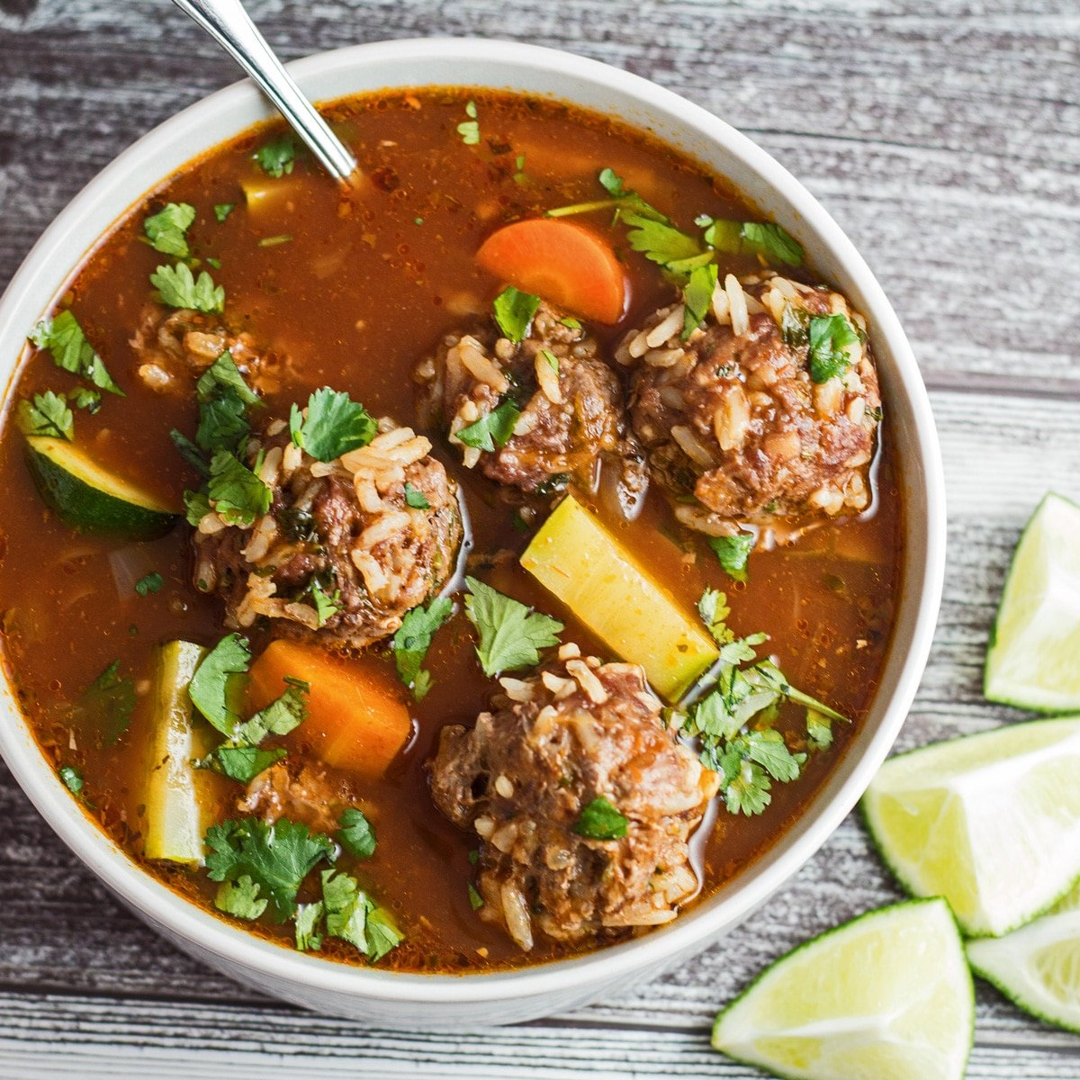 Albondigas soup with carrot, onion, potato, and zucchini.