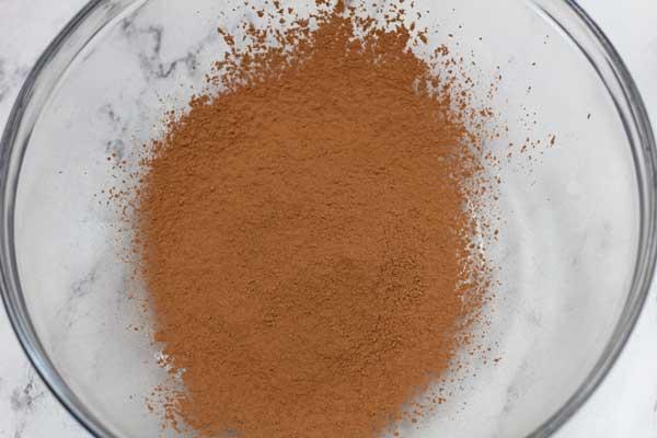 Lavorare la foto 1 della polvere di cacao setacciata in una grande ciotola.