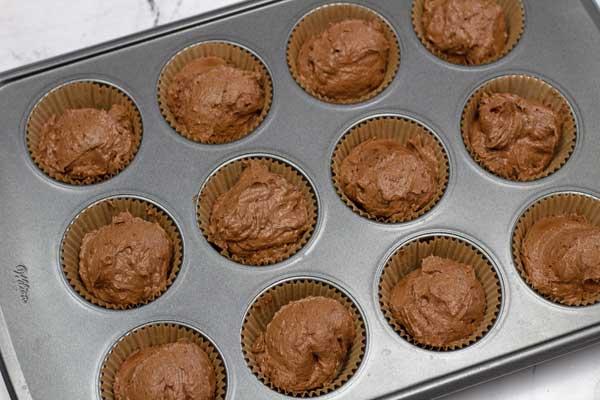Lavorare la foto 10 dell'impasto porzionato in uno stampo da muffin foderato.