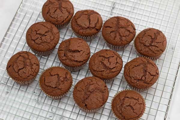 Elaborare la foto 12 dei cupcakes che si raffreddano su una griglia di raffreddamento a filo.