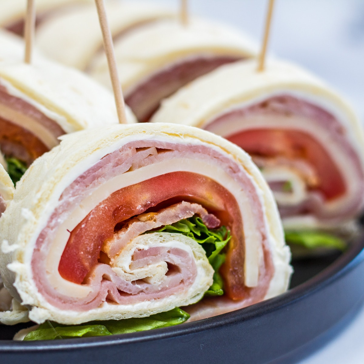 Club pinwheel sandwiches sliced and served on black plate.