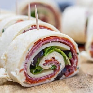 Italian pinwheel sandwiches sliced on wooden cutting board.