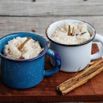 Arroz con Leche served in mugs on wooden cutting board.