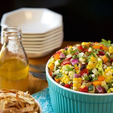 Mexican chopped salad served in blue bowl with dark background.