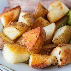Crispy oven roasted potatoes served on platter with roast and vegetables.