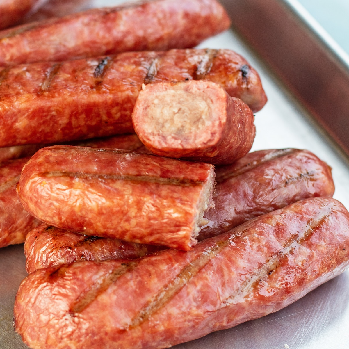 Smoked brats served on metal tray.