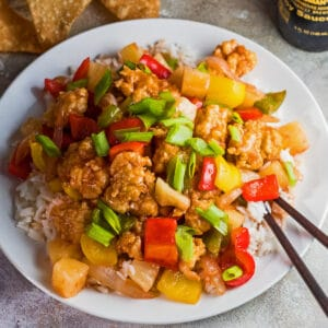 Tasty sweet and sour chicken served over rice on a white plate.