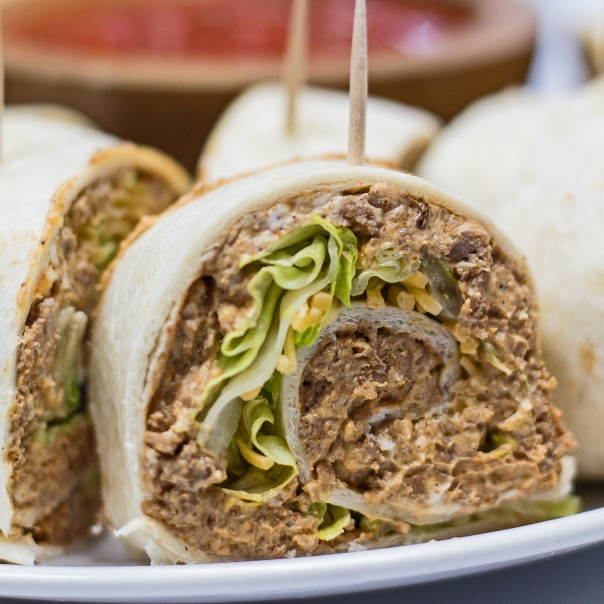 Taco pinwheel sandwiches cut and served on white plate.