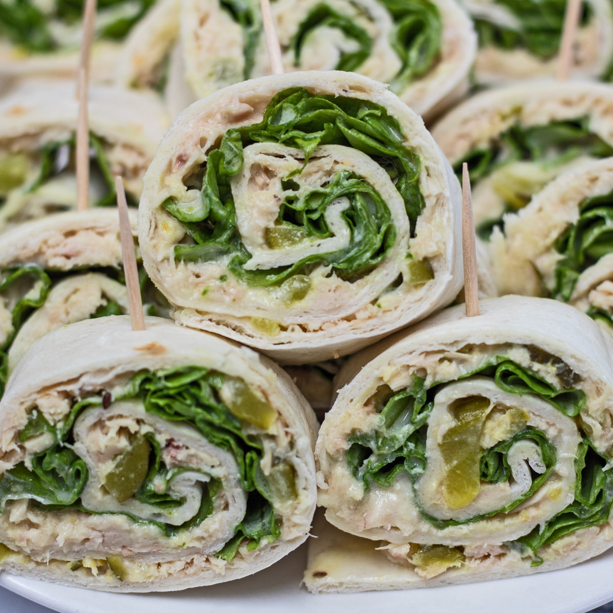 Tuna salad pinwheel sandwiches cut and stacked on plate.