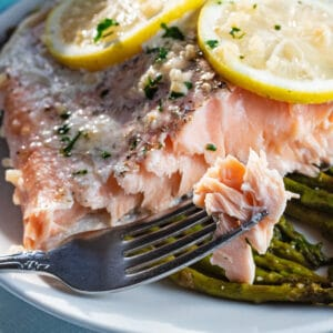 Baked salmon in foil served with asparagus on white plate.