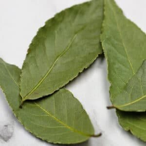 Dried bay leaves shown on light background.