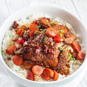 Rich and flavorful brown stew chicken served over rice in white bowl.