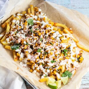 Loaded elotes-style corn fries served in baking sheet on parchment paper.