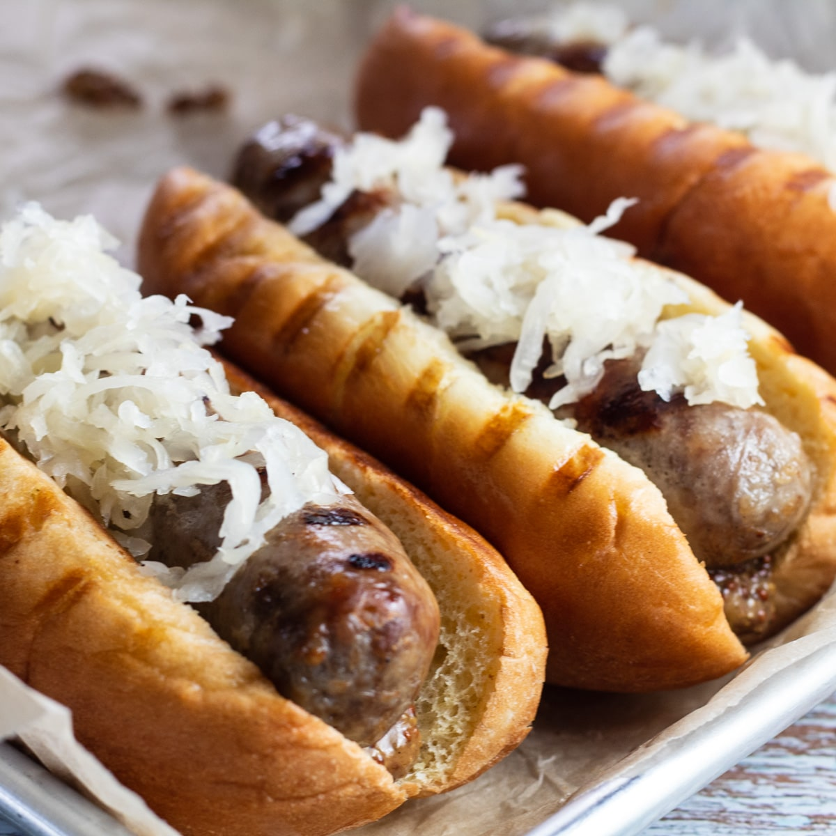 Grilled brats served on tray with German mustard and sauerkraut.