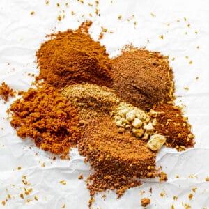Ingredientes de especias mezcladas apilados en papel de pergamino blanco.